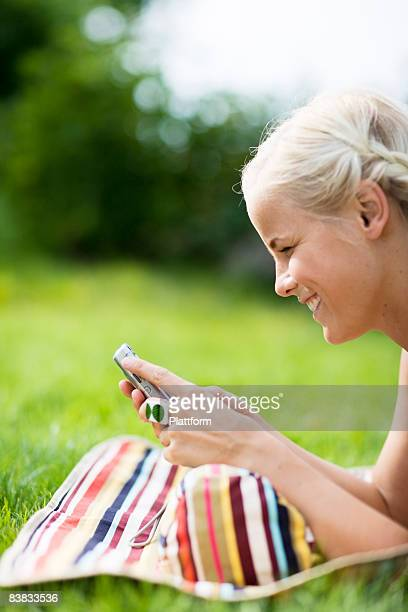 A woman lying on a lawn using a mobile phone Sweden.