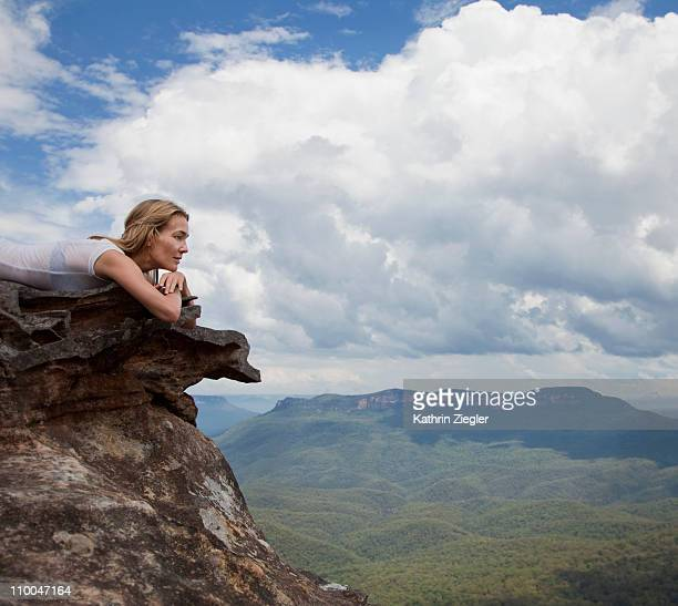 woman lying on a rock, overlooking valley