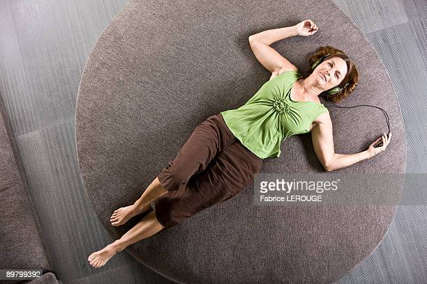 Woman lying on a round sofa and listening to headphones