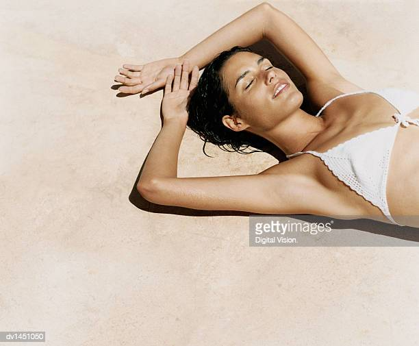 Woman Lying on a Sandy Beach Sunbathing With Her Hands Behind Her Head