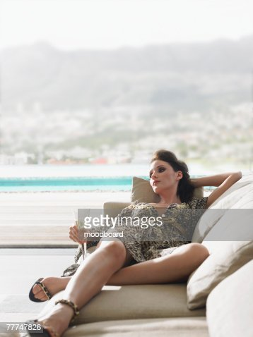 Woman Lying on a Sofa and Drinking Champagne