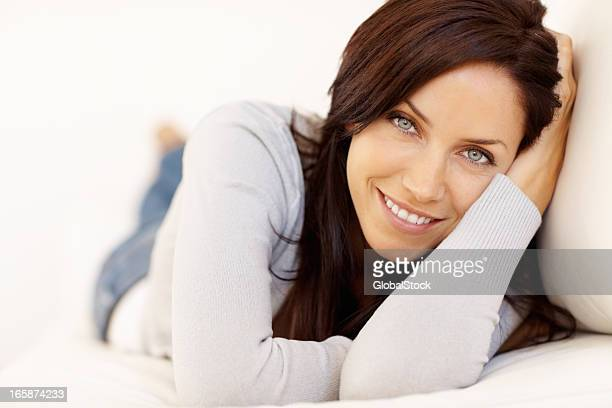 Woman lying on a sofa and smiling