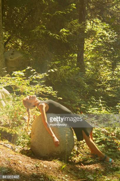 Woman lying on a stone in the forest