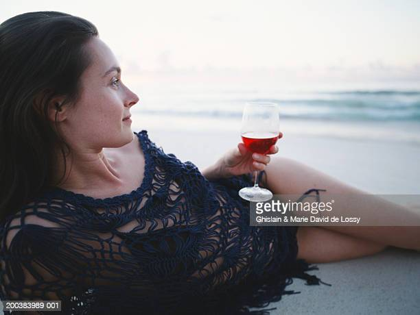 Woman lying on beach, holding glass of red wine