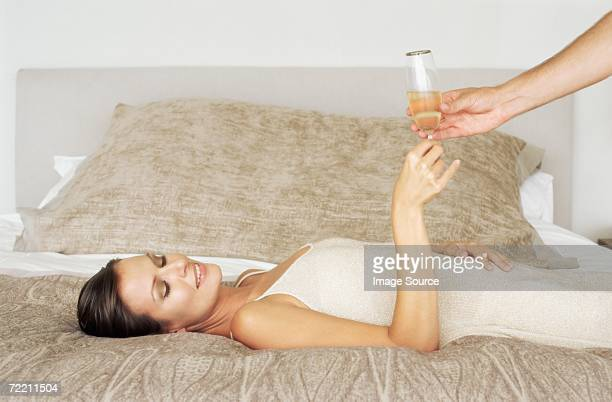 Woman lying on bed and taking champagne glass