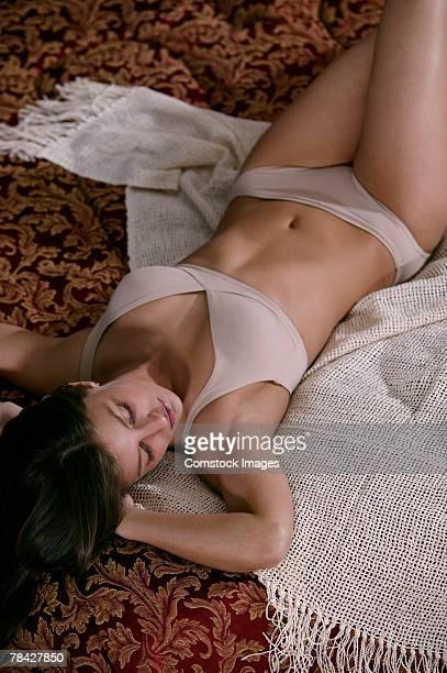 Woman lying on bed in underwear