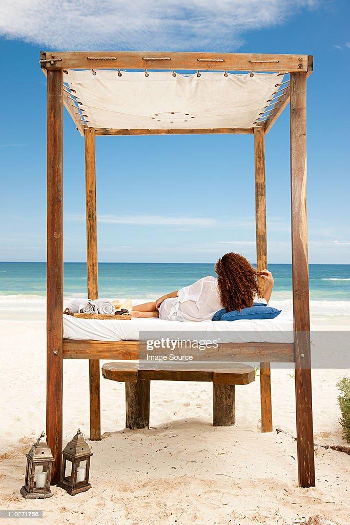 Woman lying on bed on sandy beach : Stock Photo