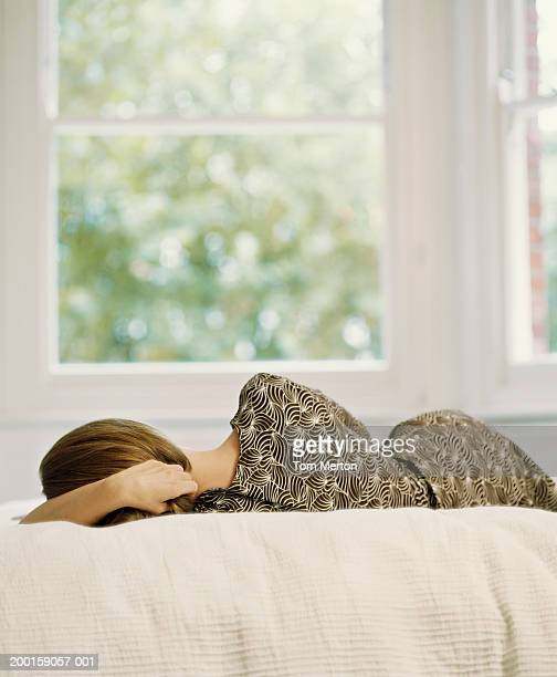 Woman lying on bed, rear view