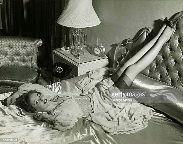 Woman lying on bed with legs on backrest, (B&W), elevated view