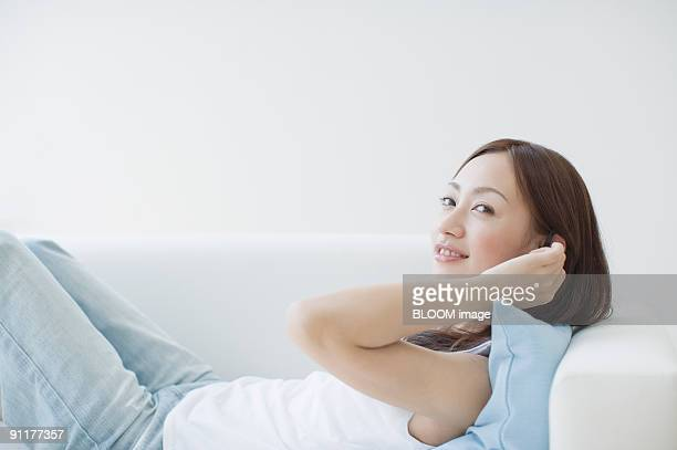 Woman lying on couch, smiling