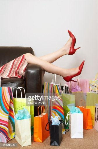 'Woman lying on couch surrounded by shopping, low section' : Stock-Foto