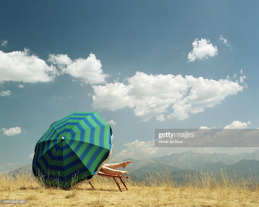 Woman lying on deckchair behind parasol in mountainous landscape : Stock Photo