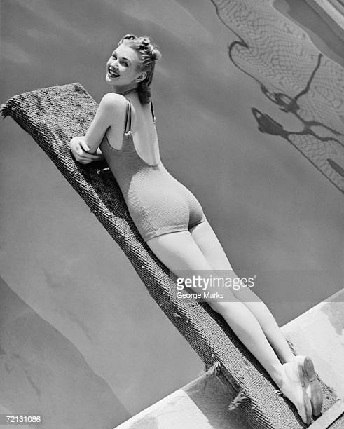 Woman lying on diving board (B&W), elevated view, portrait