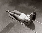 Woman Lying On Diving Board Over Pool Sunbathing Two Piece Bathing Suit Summer.