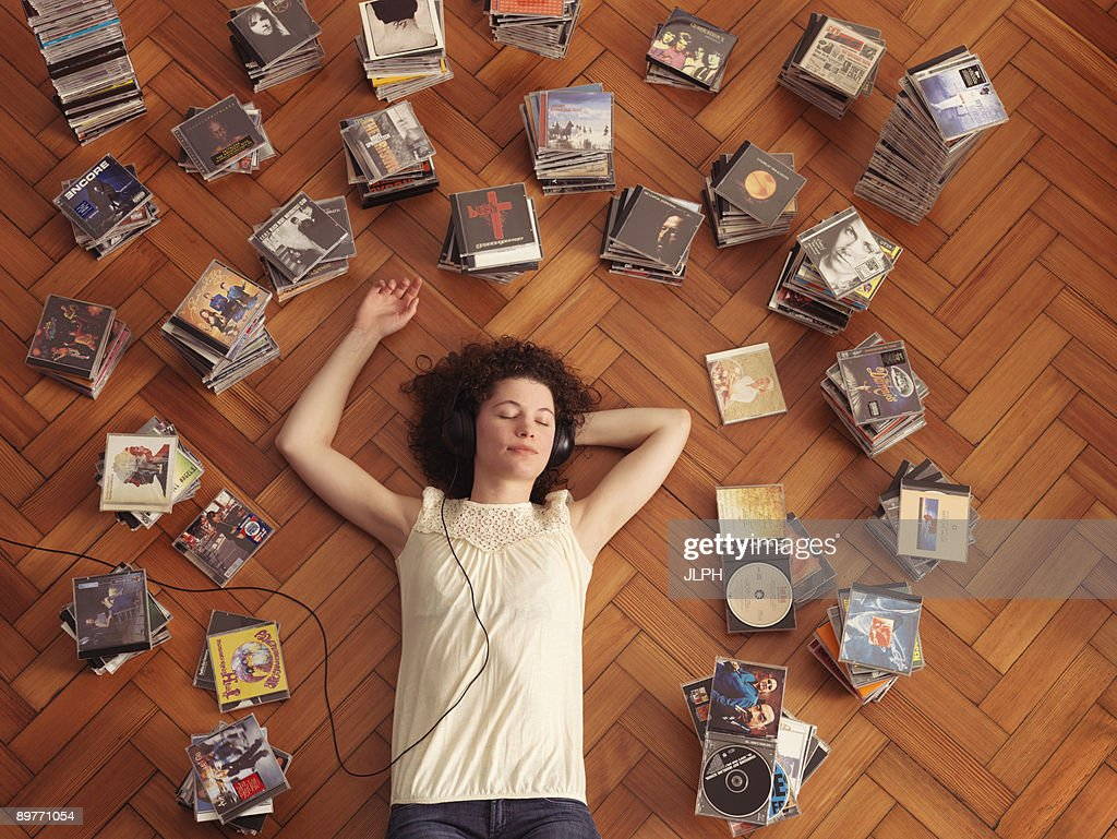 Woman lying on floor, listening to music : Stock Photo