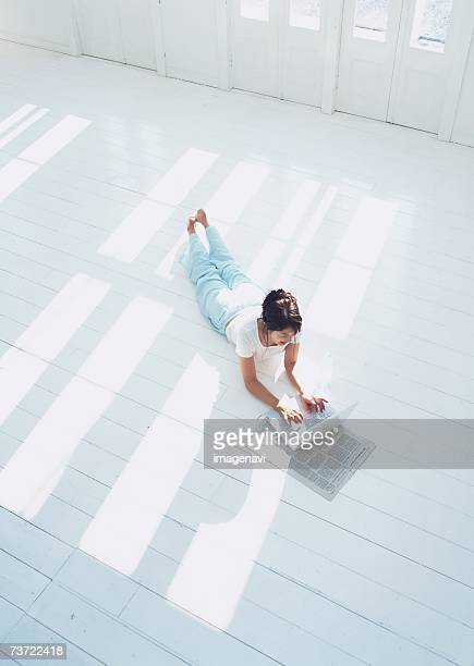 Woman lying on floor with laptop