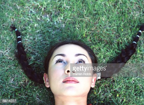 Woman lying on grass, close-up, elevated view