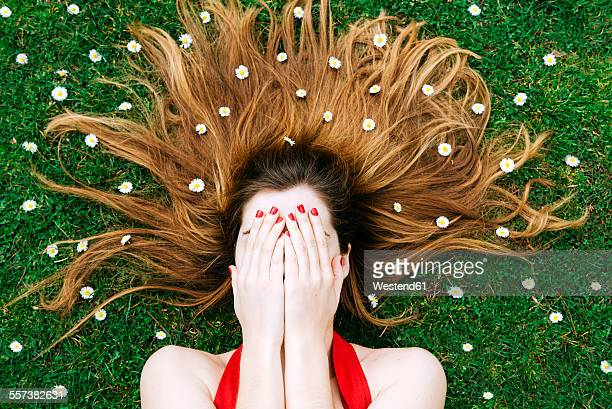 Woman lying on grass in spring with hands on face and flowers on hair