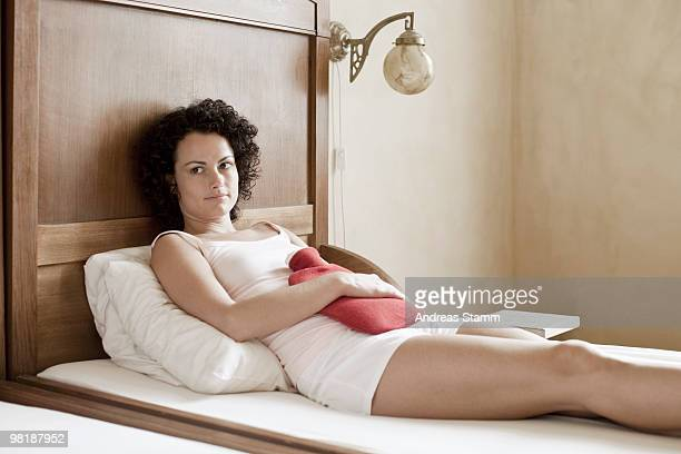 A woman lying on her bed with a hot water bottle on her stomach