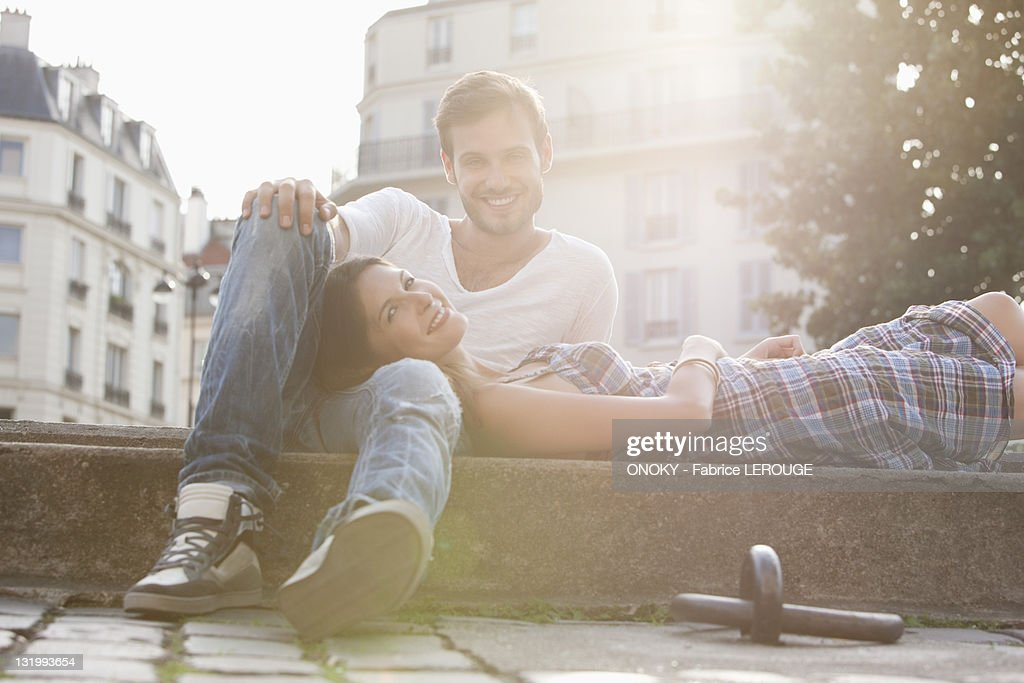 Woman lying on lap of a man at the ledge of a canal, Paris, Ile-de-France, France : Stock Photo