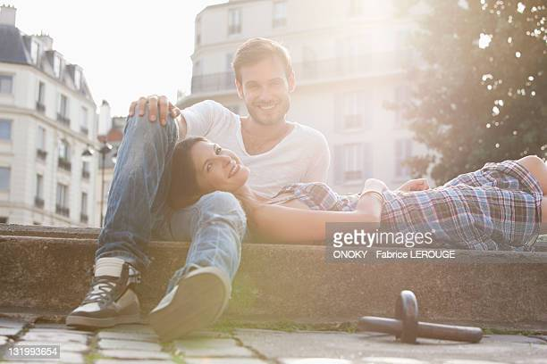 Woman lying on lap of a man at the ledge of a canal, Paris, Ile-de-France, France