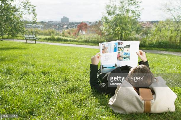 Woman lying on lawn reading a magazine