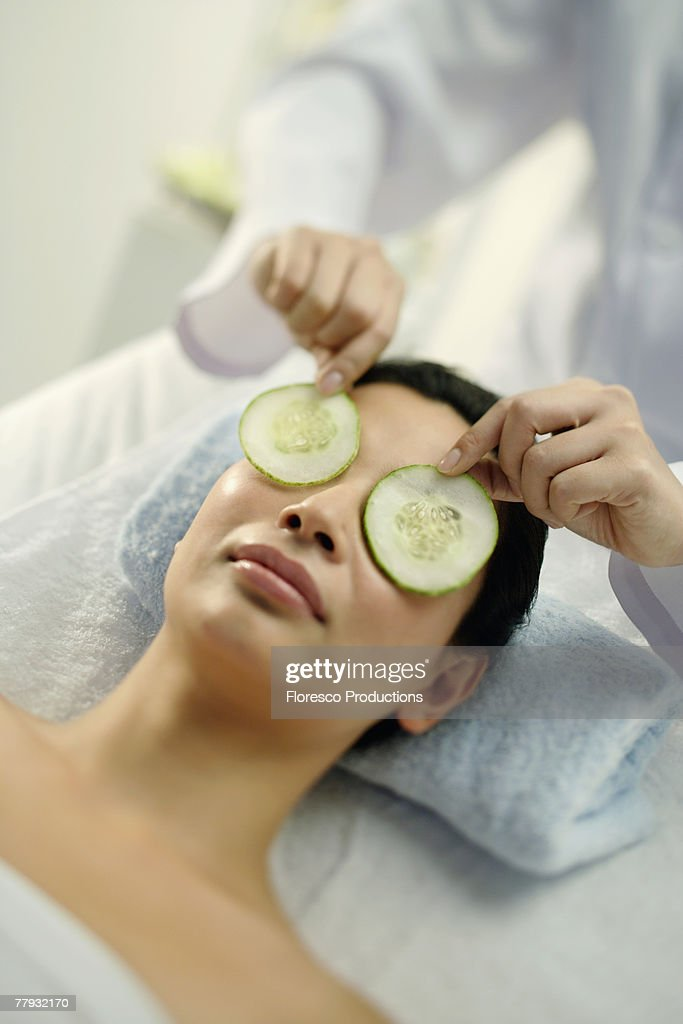 Woman lying on massage table having cucumbers placed over eyes : Stock Photo