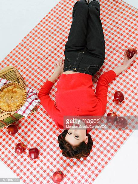 Woman lying on picnic blanket holding apple