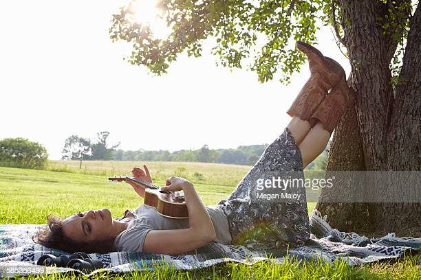 Woman lying on picnic blanket in field playing ukulele