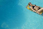 Woman lying on raft in swimming pool