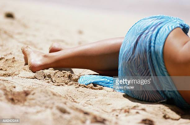 Woman lying on sand, wearing sarong, low section, rear view