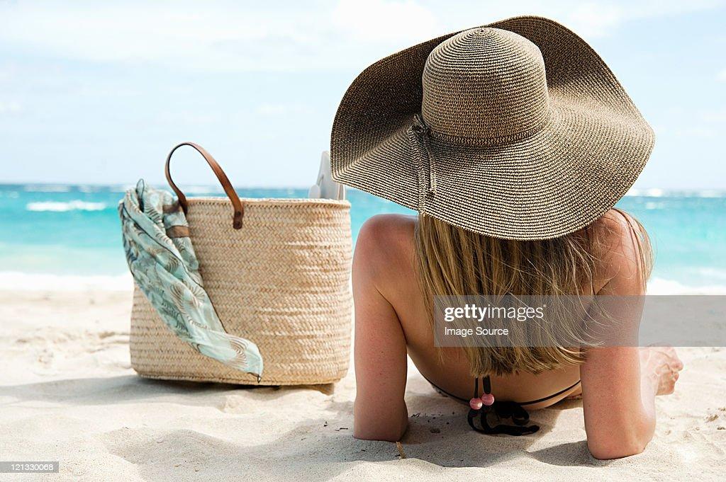 Woman lying on sandy beach, Mustique, Grenadine Islands