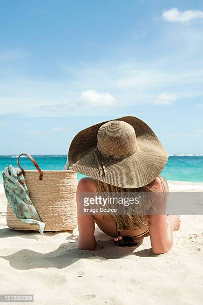 Woman lying on sandy beach, islas Grenadine Mustique,