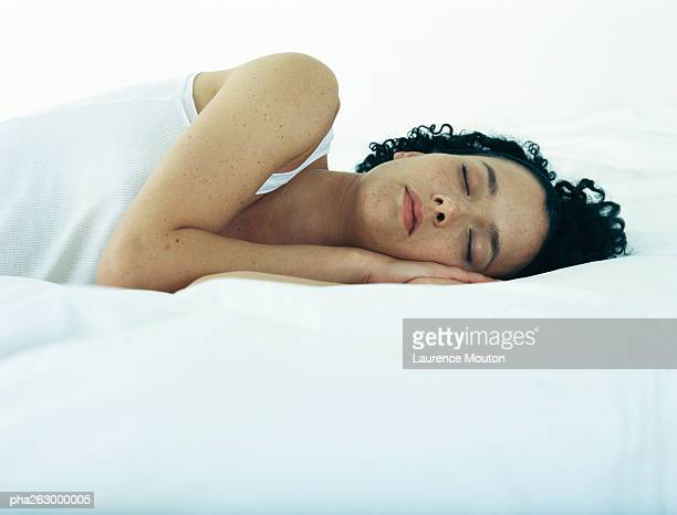 Woman lying on side on bed with hands under head and eyes closed