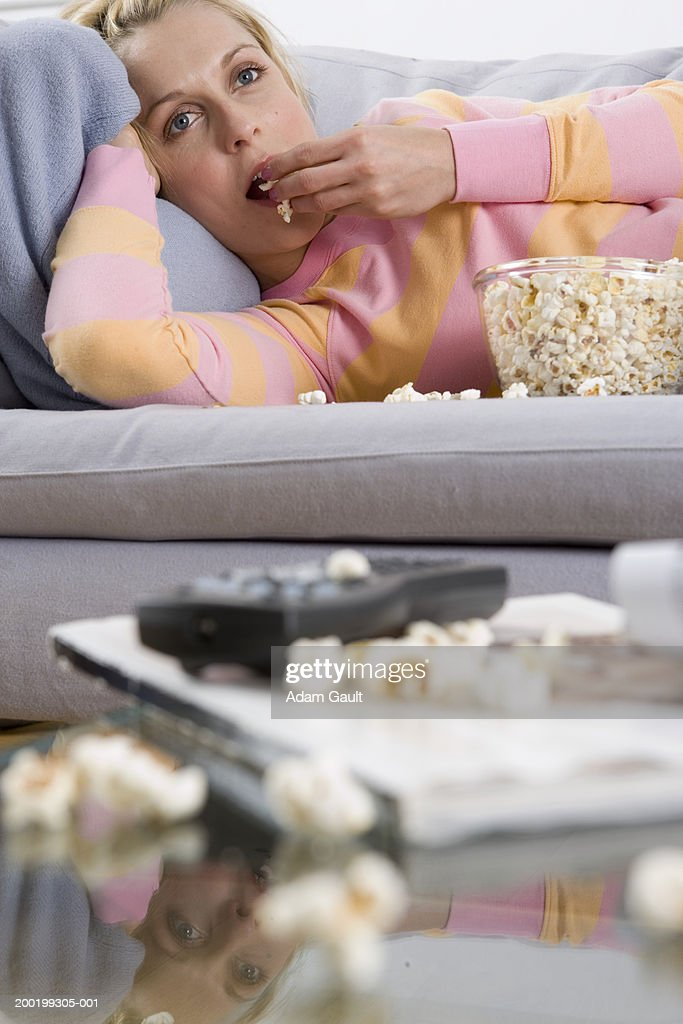 Woman lying on sofa eating popcorn, reflection in glass coffee table
