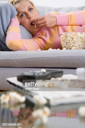 woman lying on sofa eating popcorn reflection in glass coffee table stock photo getty images. Black Bedroom Furniture Sets. Home Design Ideas