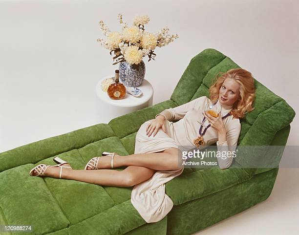 Woman lying on sofa holding wine glass, smiling, portrait