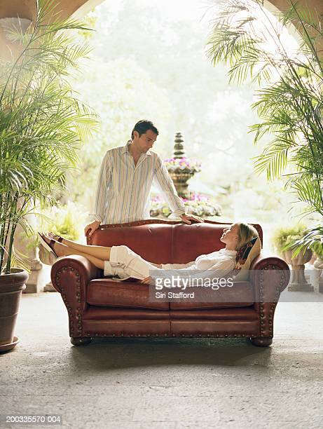 Woman lying on sofa in hotel lobby, man standing behind