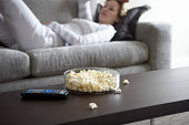 Woman lying on sofa (focus on popcorn and remote control on table)