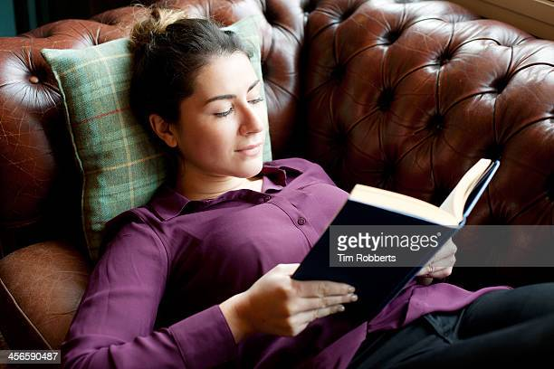 Woman lying on sofa reading book.