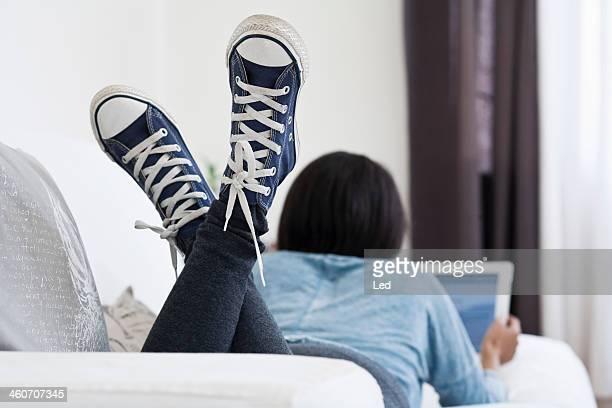 Woman lying on sofa using digital tablet
