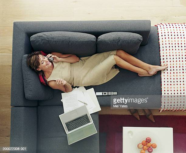 Woman lying on sofa using telephone, overhead view