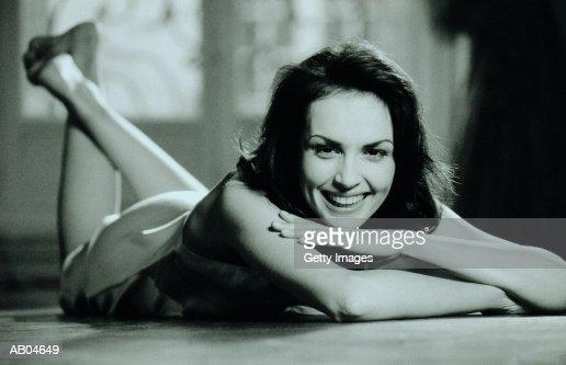 Woman lying on stomach on floor, portrait : Stock Photo