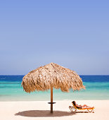 Woman lying on sun lounger on beach