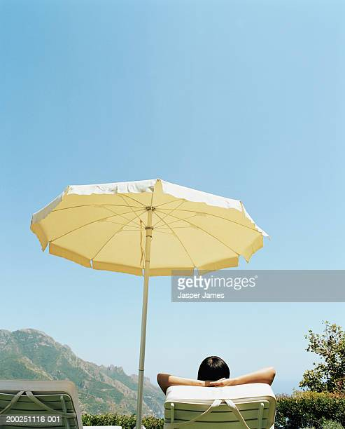 Woman lying on sunbed under umbrella, rear view