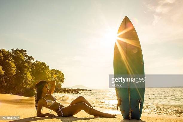 Woman lying on the beach with a surfboard, Bali, Indonesia