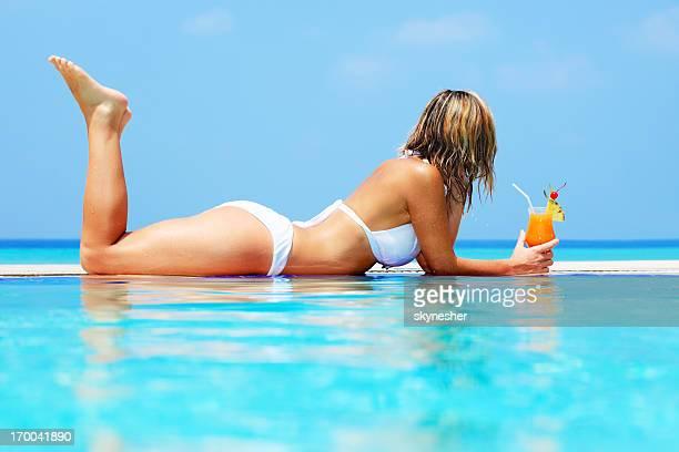 Woman lying on the edge of swimming pool.
