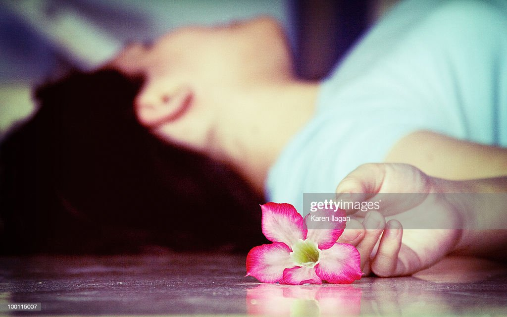 Woman lying on the floor with a pink kalachuchi : Stock Photo