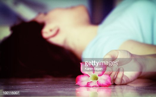 Woman lying on the floor with a pink kalachuchi : Stock-Foto