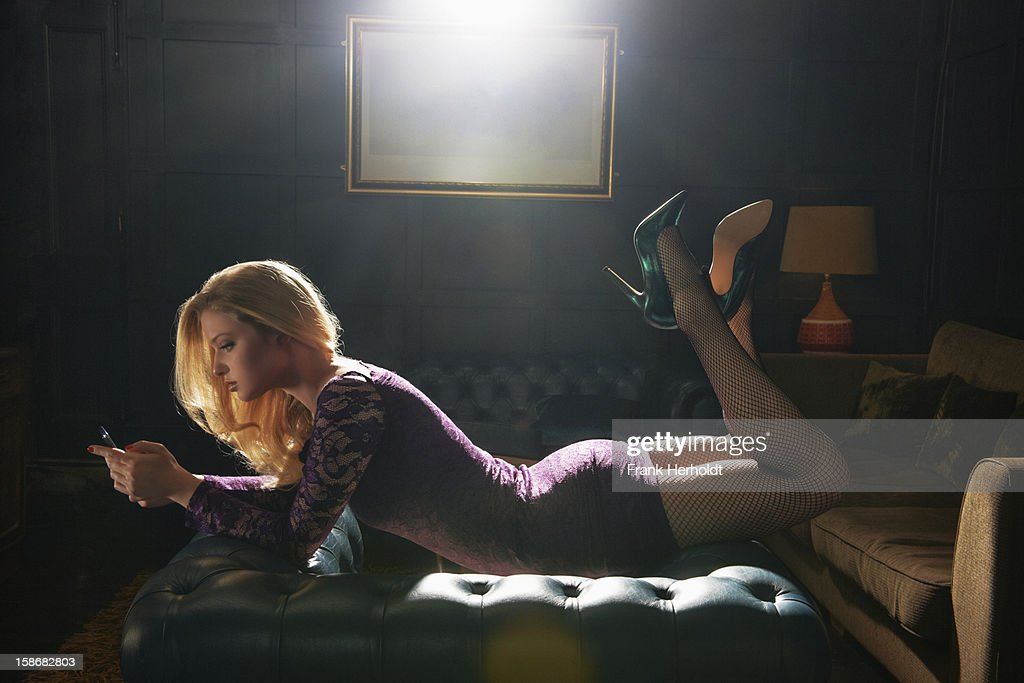 Woman lying on top of armchair with phone : Stock Photo